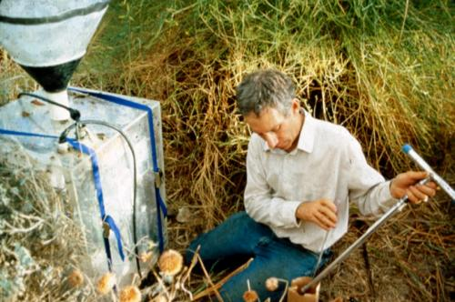 Checking soil moisture next to a device that measures carbon dioxide released by soils, Biosphere 2, 1991-1993.
