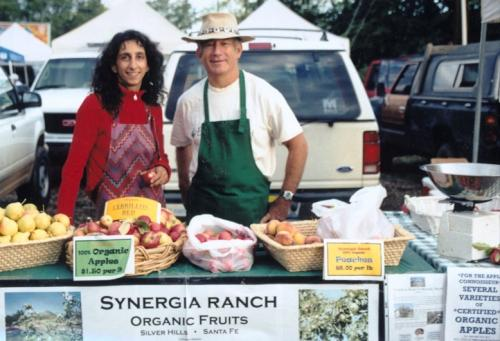 Thrity Vakil and Mark Nelson at Synergia Ranch booth, Santa Fe Farmer's Market with organic fruits and vegetables, 2006.